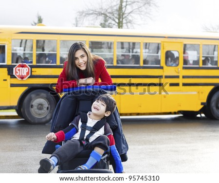 Big sister with disabled brother in wheelchair by school bus - stock photo