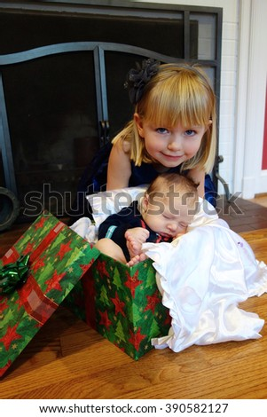 big sister with new baby brother present christmas - stock photo
