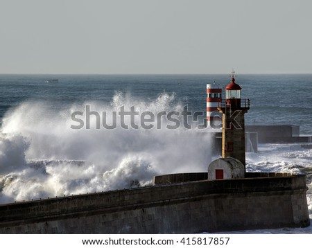 Big splashing waves with spray over piers and beacons of Douro river mouth in a sunny morning, Porto, north of Portugal - stock photo