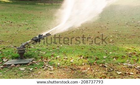 Big sprinkler spraying water in green park - stock photo