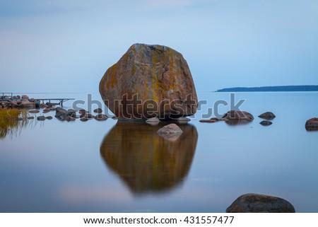 Big stone at Baltic sea at night - stock photo