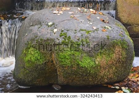 Big stone atthe creek with moss - stock photo
