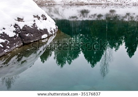 Big stone covered a snow in nonfreezing blue lake - stock photo