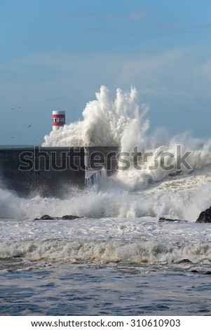 Big stormy sea wave against pier and beacon in a beautiful sunny morning. Mouth of Douro river, Porto, Portugal. - stock photo