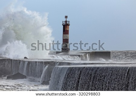 Big stormy sea waves over a pier and beacon from a river mouth in northern Portugal against blue sky  - stock photo