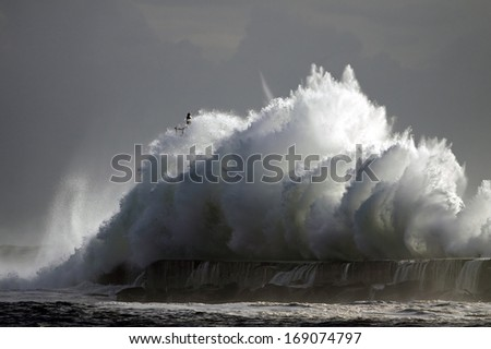 Big stormy wave against pier and lighthouse - stock photo