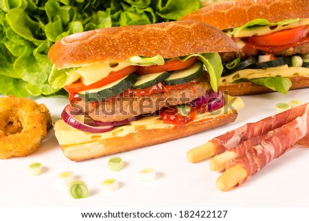 Big stuffed sandwich with beef meat,cheese and vegetables on white background.Selective focus on the sandwich - stock photo
