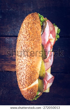 Big submarine sandwich with salami,cheese and pickles from above on wooden background,selective focus  - stock photo