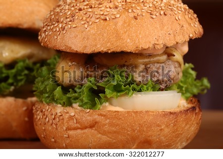 Big tasty appetizing fresh burgers of green lettuce red tomato cheese and bacon slice meat cutlet and white bread bun with sesame seeds closeup, horizontal picture - stock photo