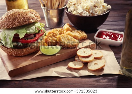 Big tasty hamburger with snacks and glass bottle of light beer on wooden table - stock photo
