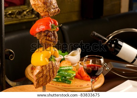 Big tasty roasted meat cuts at skewer on a decorated table - stock photo