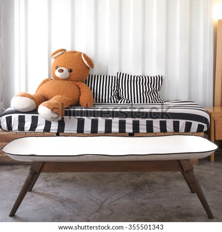 Big Teddy Bear Plush Doll sitting on the sofa with black and white stripe pillows - stock photo