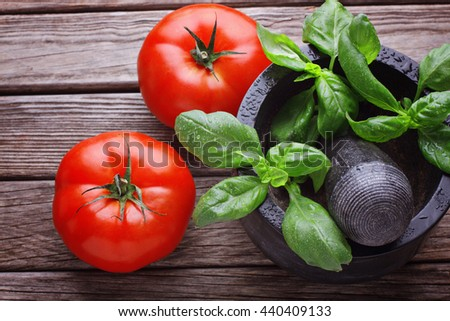 Big tomatoes with basil in mortar - stock photo
