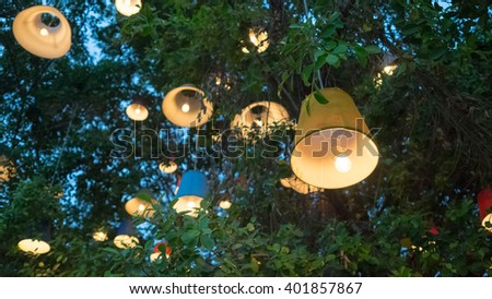 Big tree decorated with retro lamps. - stock photo
