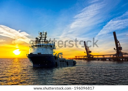 Big tugboat in a harbor at sunrise. - stock photo