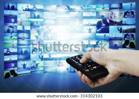 Big TV panel with television stream images and remote control in hand - stock photo
