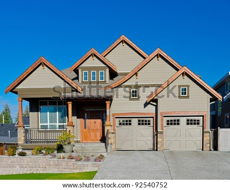Big, two garage doors, luxury home in suburbs, against dark blue sky. - stock photo