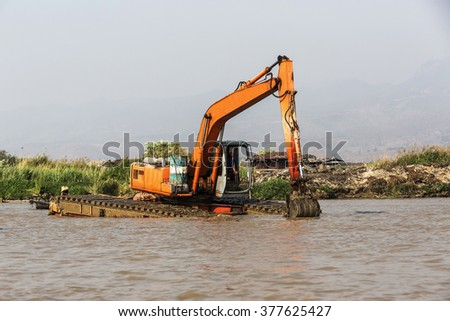Big water excavator dredging sediment mud from river. - stock photo