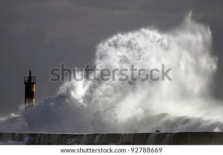 Big wave against lighthouse in the north of Portugal in a stormy overcast evening, with interesting light - mouth of river Ave in Vila do Conde - stock photo