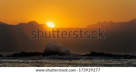 Big wave front with bubbles and splashes at sunset - stock photo