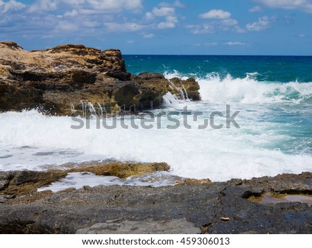 Big waves on rock coast blue sea and sky on Crete, Greece - stock photo