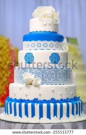 Big wedding cake decorated with blue flowers - stock photo