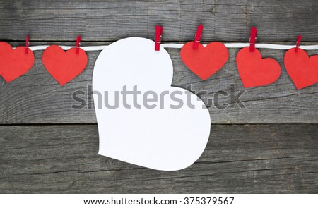 big white Heart and red little hanging on the clothesline. Space for info text. On color background. Romantic date, invitation card, Happy Valentines Day concept. Toned image - stock photo
