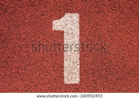 Big white track number on red rubber racetrack. Gentle  textured running racetracks in small outdoor stadium. - stock photo
