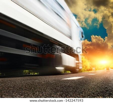 big white truck on the asphalt road - stock photo