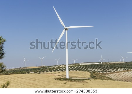 Big windmill in the foreground, with other windmills, olive groves and farm in the background - stock photo
