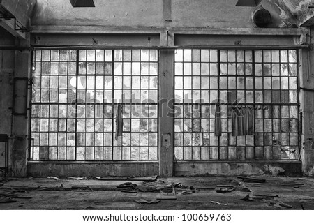 big windows in the broken and abandoned factory black and white - stock photo