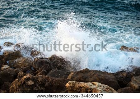 Big windy waves splashing over rocks. Storm begins. - stock photo