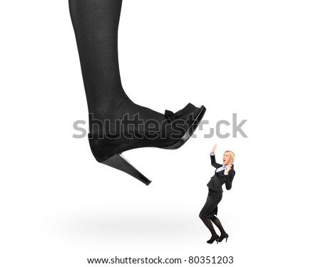 Big woman shoe stepping on an affaraid businesswoman isolated on white background - stock photo