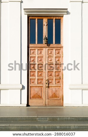 Big wooden church closed door and white walls - stock photo