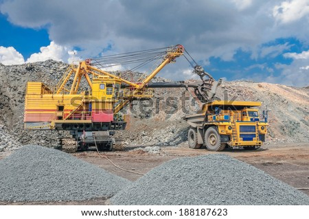 big yellow excavator extracting iron ore in opencast mine and loading heavy truck - stock photo