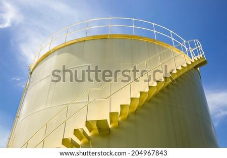 Big yellow tank under blue sky  - stock photo