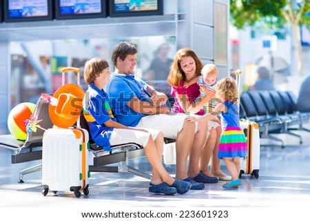 Big young family with three kids traveling by airplane at Dusseldorf International airport, parents with teenager boy, toddler girl and little baby holding colorful luggage for summer beach vacation  - stock photo