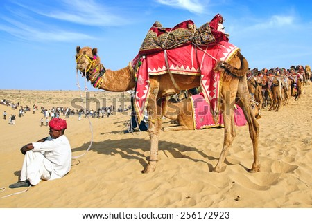 BIKANER, INDIA - JANUARY 09, 2012: Cameleer with camel at the dunes during the festival. Bikaner Camel Festival is an annual festival dedicated to the surly, hardy animal.   - stock photo
