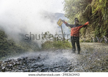 "Bike adventure travel photo. Bike tourist  on the ""road of death"" enjoys the waterfall. - stock photo"