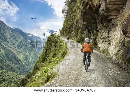 "Bike adventure travel photo. Bike tourists  ride on the ""road of death""  downhill track  in Bolivia. In the background sky circles a condor over the scene. - stock photo"