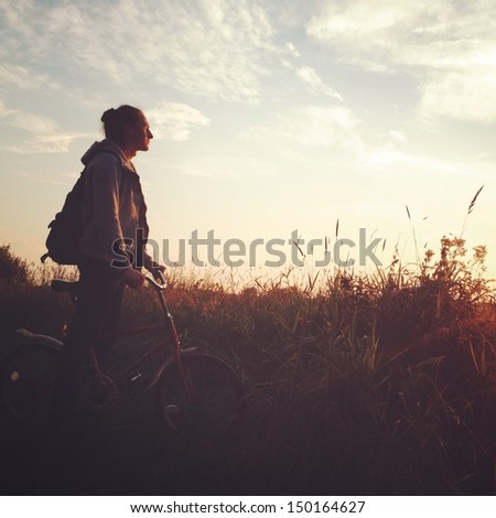Bike  at the sunset on the meadow  - stock photo