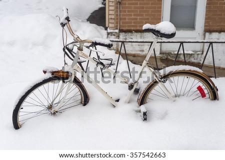 Bike covered with fresh snow in Montreal during snow storm in 2016 - stock photo