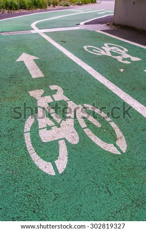 Bike lane signs painted onto a green bike lane in Melbourne, Australia. - stock photo