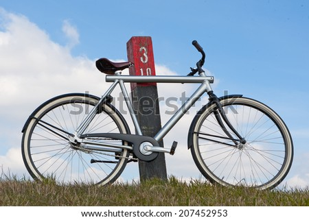 Bike leaning against pole on a dike in the Netherlands - stock photo