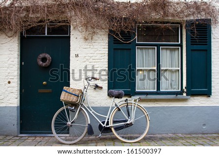 Bike leaning on a wall, Brugge, Belgium.  - stock photo