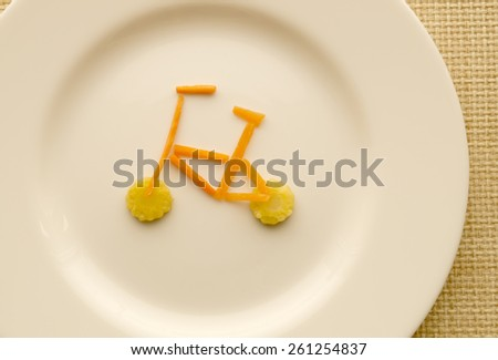 Bike of carrot and of corn on a white plate - stock photo