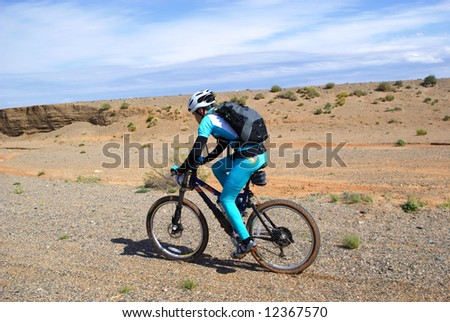 Bike racer in desert mountains - stock photo