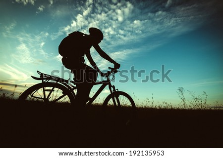 bike silhouette on the background of sky and fields at sunset - stock photo