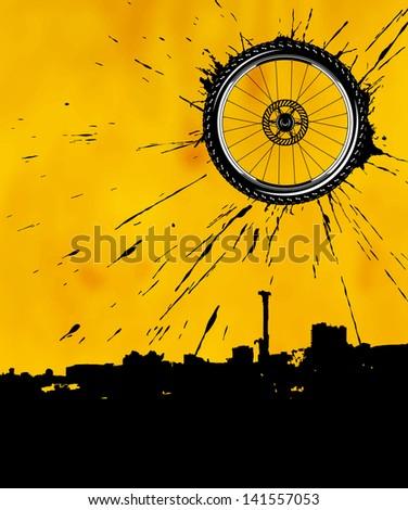 Bike wheel as the sun over the city - stock photo