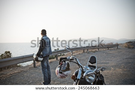 biker and motorcycle by the sea in vintage tone effect - stock photo